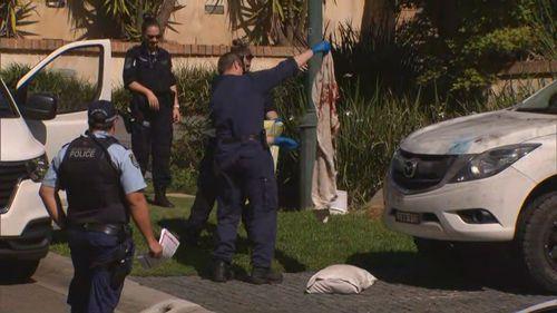 Police officers establish a crime scene at the Sydney property.
