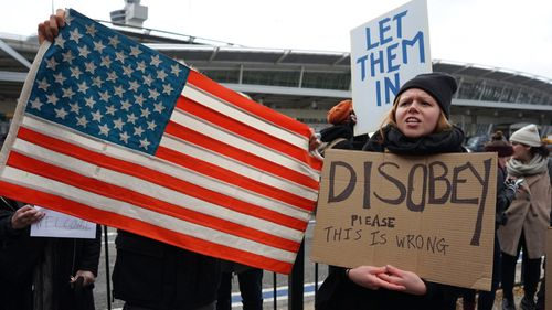 Protesters gather outside New York's JFK airport. (AAP)