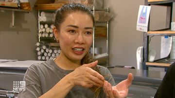 A Queensland bakery owner has described the moment she was shot in the back during an alleged armed robbery on Father's Day.Kim Phran was behind the counter at her bakery in Ipswich when men allegedly stormed the bakery armed with rifles on Sunday.