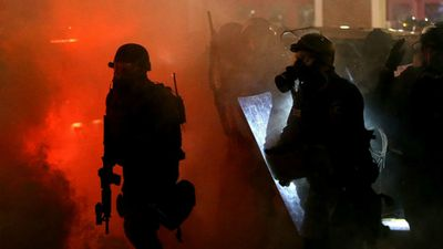 Riot police advance under a cloud of tear gas. (Getty Images)