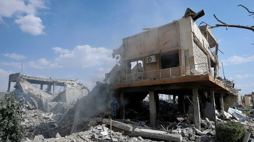 A fireman extinguishes smoke that rises from the damage of the Syrian Scientific Research Center which was attacked by US, British and French military strikes. (AP)