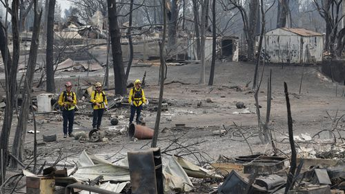 Much of the landscape has been reduced to blackened trees and smouldering rubble. Picture: AP
