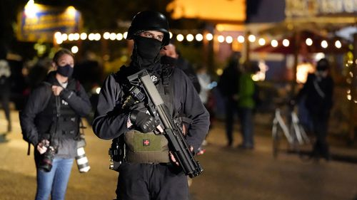 A person carries a gun while marching on the night of the election, Tuesday, Nov. 3, 2020, in Portland, Ore