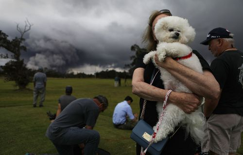 A woman picks up her dog as others watch the eruption. (Getty)