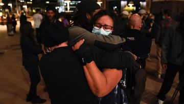 Three film industry workers comfort one another during the candlelight vigil.