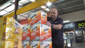 Orange Cellars manager George Eleftheriou stacking cartons of beer before his next customer arrives.