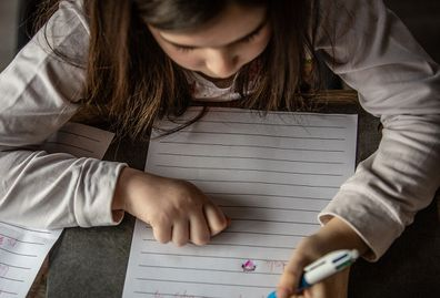 Young girl writing letter.