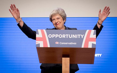 UK Prime Minister Theresa May waves to the audience at the Conservative Party conference in Birmingham.