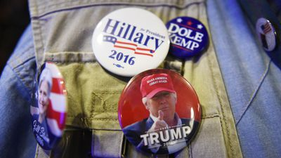 <p>A man shows off his badges at Canberra's National Press Club. </p> <p>(AAP)</p>
