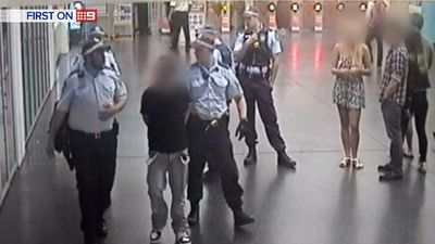 Police detain one man, who was subsequently charged with assault, while the victims look on. (9NEWS)