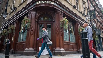 A person wearing a protective face mask walks past a temporarily closed pub named after the founding father of epidemiology John Snow, on June 19, 2020 in London, England.