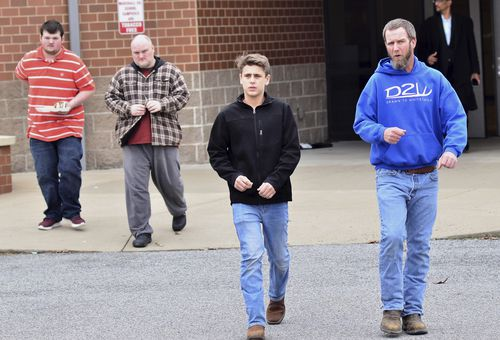 Parents escort their children out of the school after the shooting. (AAP)