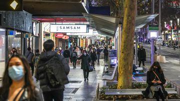 Shoppers and pedestrians in masks walk down Swanston Street in Melbourne's CBD.