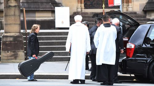 Angus Young carries a guitar as he watches the casket of his brother, AC/DC co-founder and guitarist Malcolm Young, get carried from St Mary's Cathedral in central Sydney to a waiting hearse (Image: AAP)