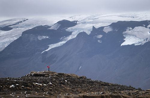 A man stops on his way to the top of what once was the Okjokull glacier, in Iceland
