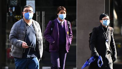 People wearing face masks walk through the city on July 20, 2020 in Melbourne, Australia.