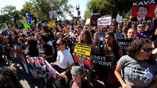 Protesters march toward the Supreme Court as they demonstrate against Supreme Court nominee Brett Kavanaugh.