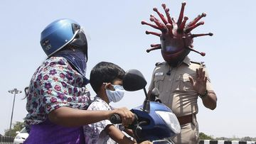 Police officer Rajesh Babu wears a helmet representing the coronavirus, and requests commuters to stay home during the 21-day countrywide lockdown.