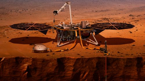 This NASA artist impression shows the InSight lander drilling into the surface of Mars.