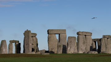 In this Tuesday, Dec. 17, 2013 file photo, visitors take photographs of the world heritage site of Stonehenge, England. The British government went against the recommendations of planning officials when it gave its consent Thursday Nov. 12, 2020, to controversial plans for a road tunnel to be built near the prehistoric monument of Stonehenge in southern England in order to ease congestion along a stretch widely prone to gridlock. (AP Photo/Alastair Grant, File)