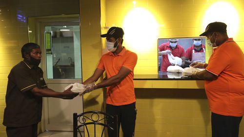 Taj al-Islam, 50 year old Bangladeshi carwash worker (left) receives his free food at a restaurant in Sharjah, United Arab Emirates.