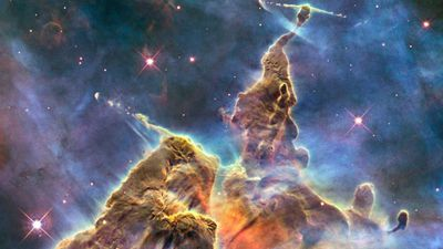 The top of a three-light-year-tall pillar of gas and the dust that is being eaten away by the brilliant light from nearby bright stars in the Carina Nebula. (AAP)
