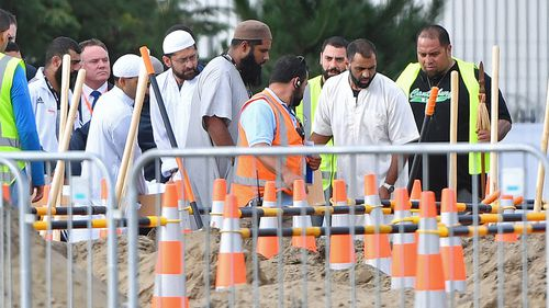 Mourners shovel dirt at the funeral of father and son, Khaled and Hamza Mustafa, the first funerals of the 50 victims of the mosque shootings, at the Memorial Park Cemetery in Christchurch.