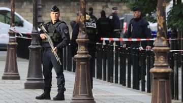 Police officers control the perimeter outside the Paris police headquarters.