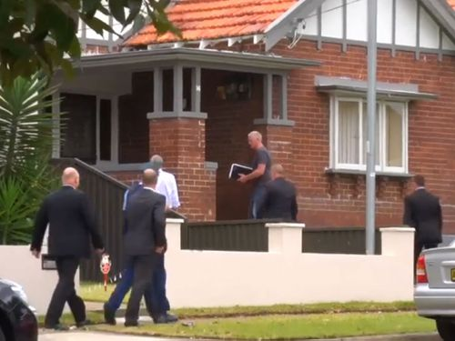 Police stand outside  the Belmore home of slain Martin Place terrorist Man Haron Monis. (9NEWS)