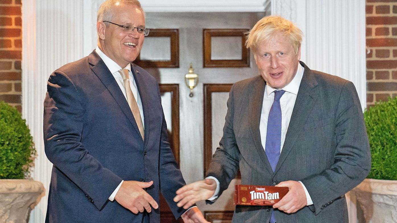 Prime Minister Boris Johnson is given a packet of the Australian snack, Tim Tams as he is greeted by his Australian counterpart, Scott Morrison on September 21, 2021 in Washington DC.