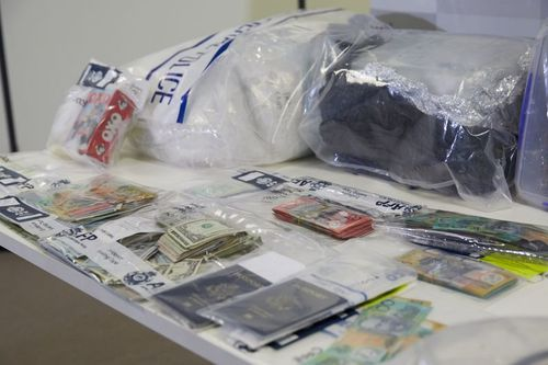 Drugs, passports and money are seen among other evidence during a police press conference in Melbourne.