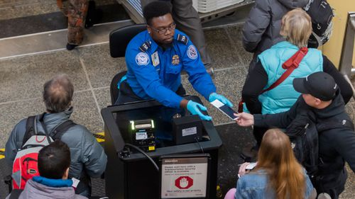 A Transportation Security Agency (TSA) agent checks the identification of air travelers at Ronald Reagan Washington National Airport as the partial shutdown drags on.