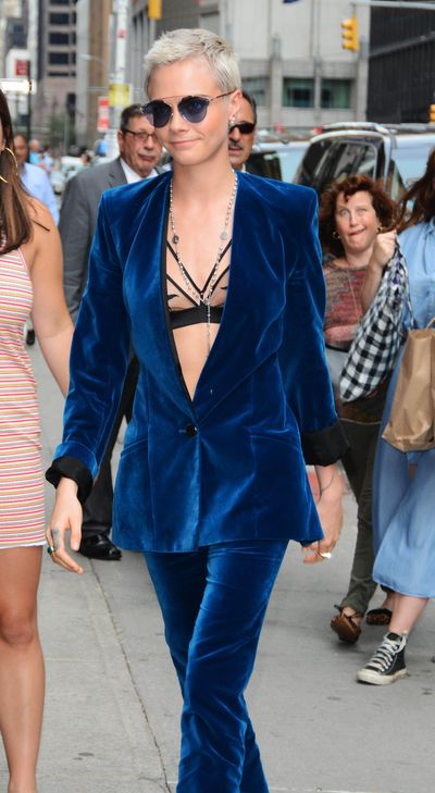 Cara Delevingne opts for a sheer bra beneath a velvet suit in New York on July 20.