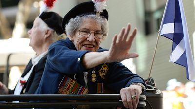 An elderly veteran waves to the crowds during an ANZAC Day parade in Brisbane. (AAP)
