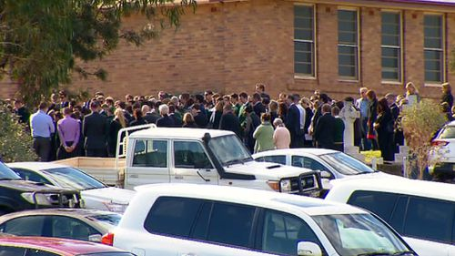 Hundreds of mourners gathered for Archie Hunt's funeral today. (9NEWS)