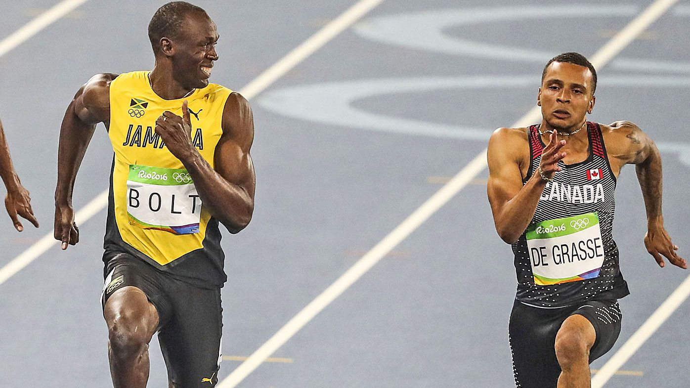Usain Bolt smiles as he looks at Andre De Grasse in the Men's 100 metre semifinal of the Rio 2016 Olympic Games