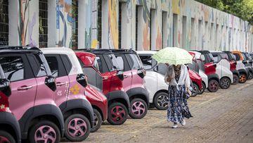 A women walks past SAIC-GM-Wuling Automobile Co. electric vehicles at a roadside parking lot in Liuzhou, China.