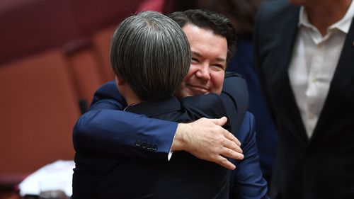 Labor senate leader Penny Wong receives a hug from Liberal senator Dean Smith. (AAP)