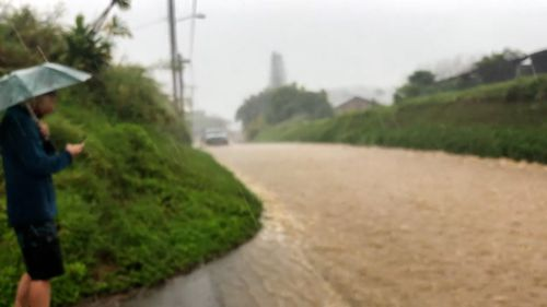 Water rushes down the street in the Maui, Hawaii, community called Haiku, on Monday.