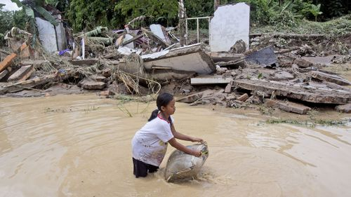 A young girl washes a pillow in flood water near ruins of houses at a neighbourhood affected by the flood in Medan, North Sumatra, Indonesia, Friday, Dec. 4, 2020