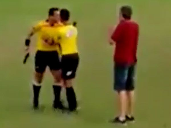 A referee threatens players and officials with a handgun. (Supplied)