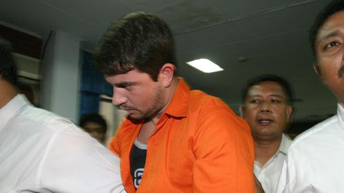 Brazilian drug smuggler Rodrigo Gularte escorted by Indonesian National Drug Bureau officers shortly after he was shown to journalists at an airport, in Tangerang, Banten, Indonesia. (AAP)