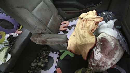 Belongings stained with blood are seen inside a car the family was traveling in,.