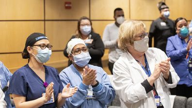 "Nurses celebrate with a standing ovation and cheer, ""Elmhurst Strong!"""