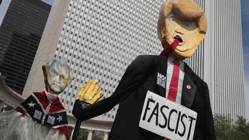 Demonstrators protesting the alt-right movement and mourning victims of the Charlottesville rally carry puppets of President Donald Trump and US Attorney General Jeff Sessions on August 13, in Chicago, Illinois. (AFP)