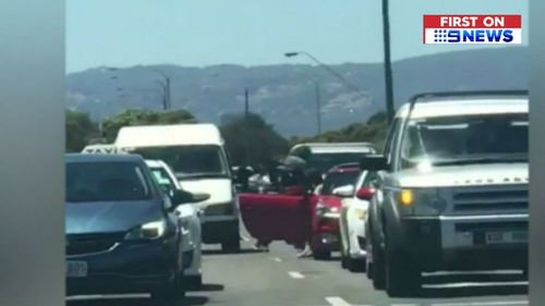 The man can be seen charging at the car as other drivers attempt to restrain him. (9NEWS)