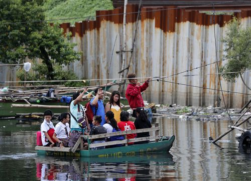 Residents on a makeshift boat make for safer areas of the capital Manila.