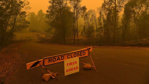 A road closure sign on the intersection of The River Road and the Kings Highway which are both closed due to the fire near Batemans Bay.
