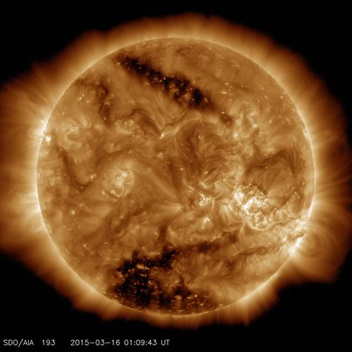 This image from NASA's Solar Dynamics Observatory on March 16, 2015, shows two dark spots, called coronal holes. The lower coronal hole, a polar coronal hole, was one of the biggest observed in decades.