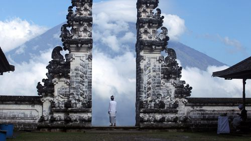 A Balinese man watches Mount Agung volcano as he stands at a temple in Karangasem, Bali. (AP)